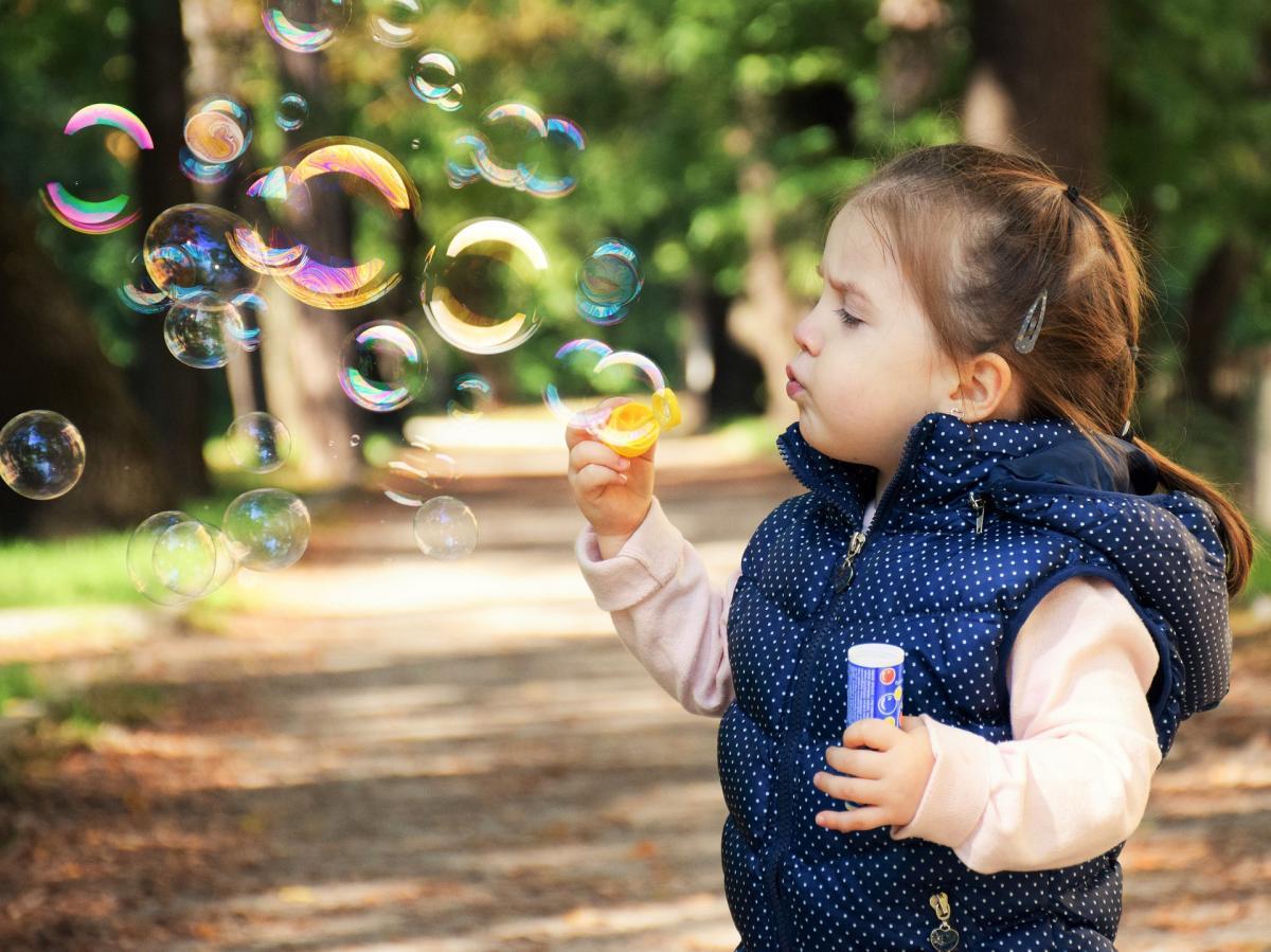 boy enjoys blowing bubbles