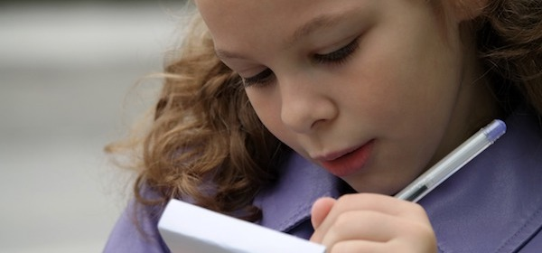 Girl writes on pad to represent cost of delivering childcare