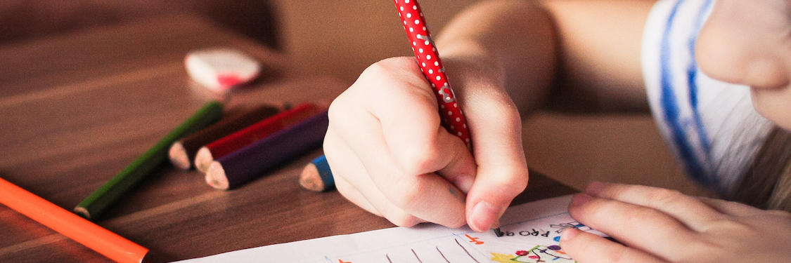 A child draws with pencils close up