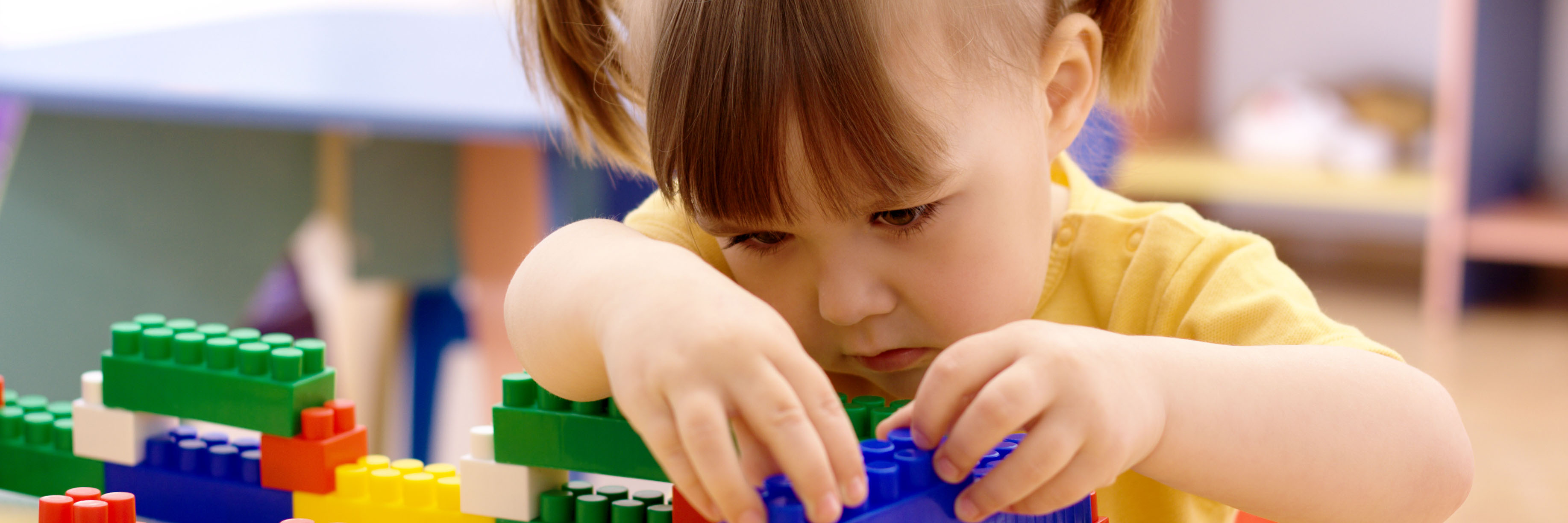 a young girl concentrates on building blocks