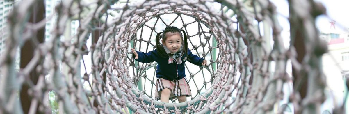 Girl in play tunnel in playground to illustrate 30 hours childcare article