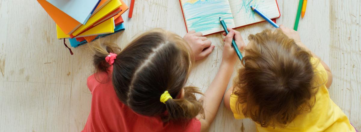girls scribbling in book