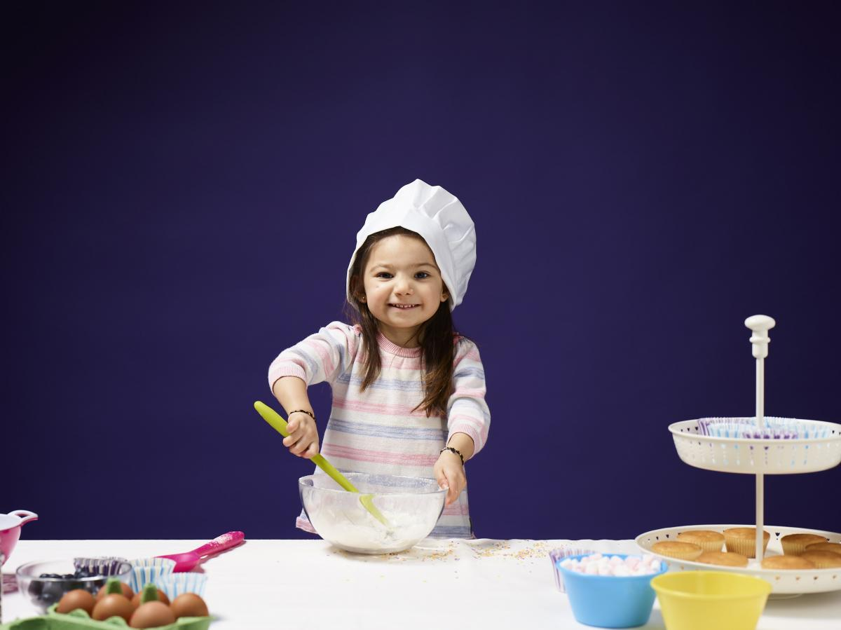 a young girl enjoys baking, mixing ingredients