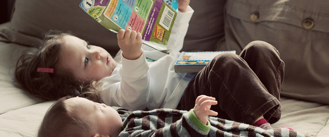 Child reading to a baby