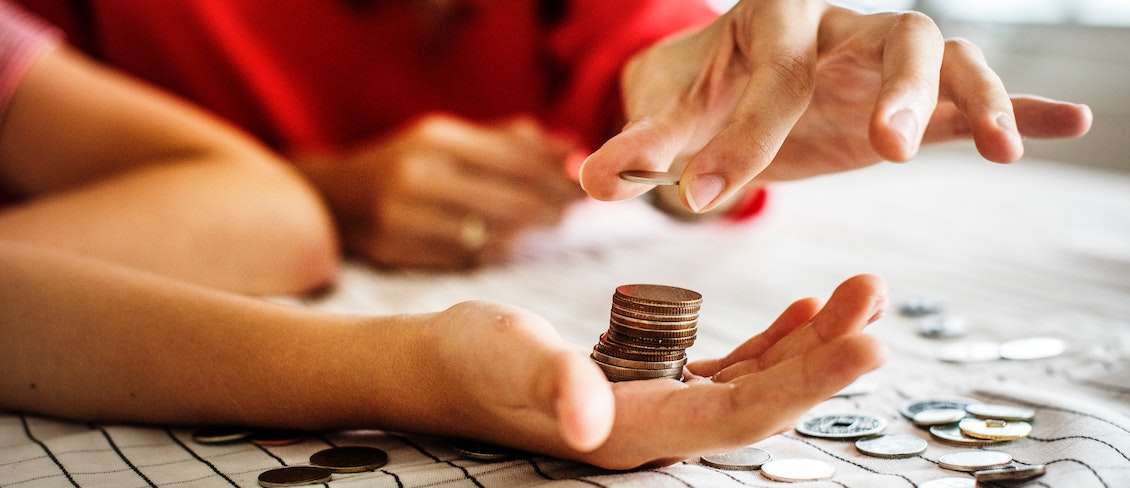 Woman counts out coins - how will minimum wage increases affect your nursery or early years business?