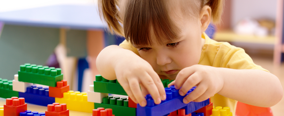Little girl building with blocks