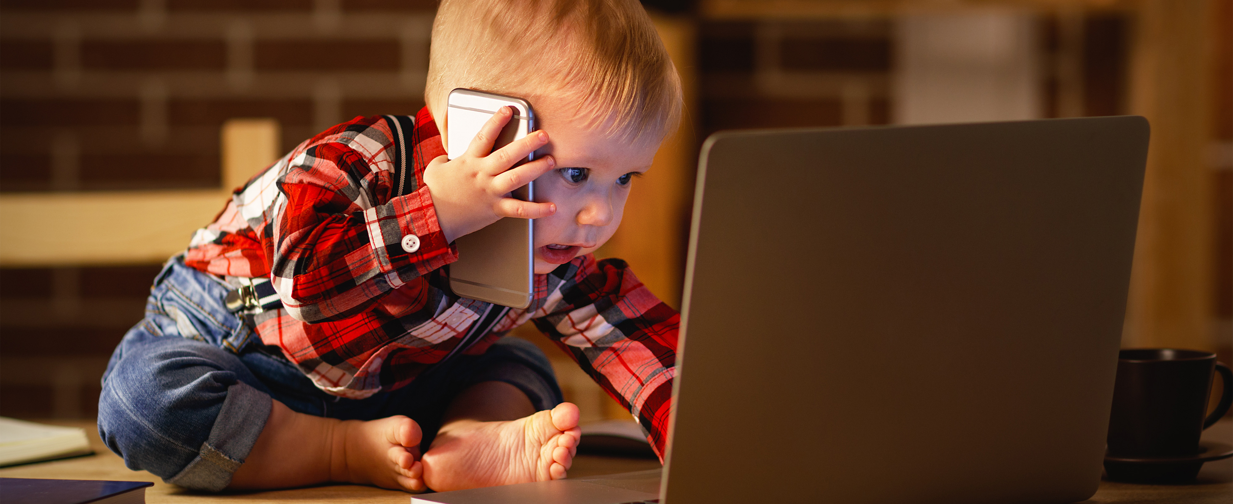 a toddler plays with a laptop and mobile phone