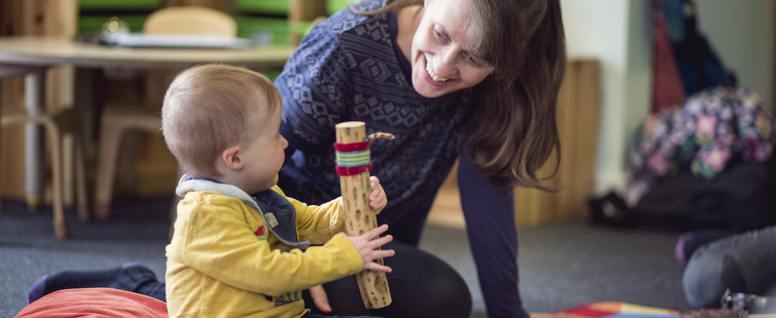 A woman plays with baby at Pre-school Learning Alliance play session