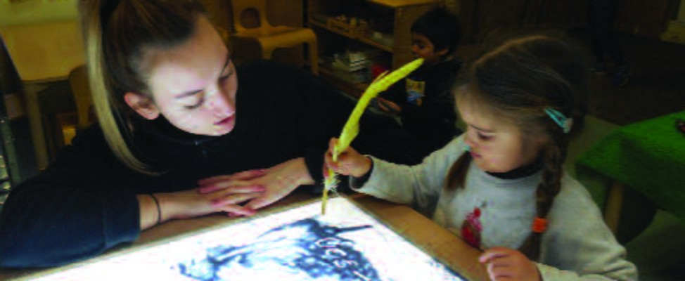 Ellie Lloyd exploring the potential of a feather and paint with a young learner