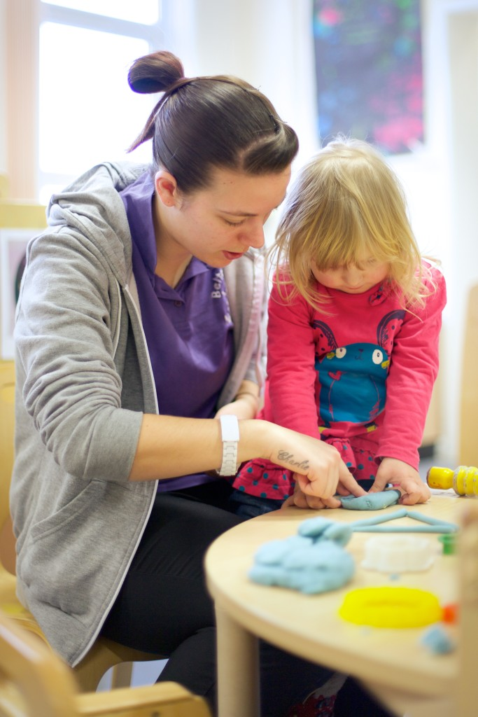 Nursery worker plays with little girl
