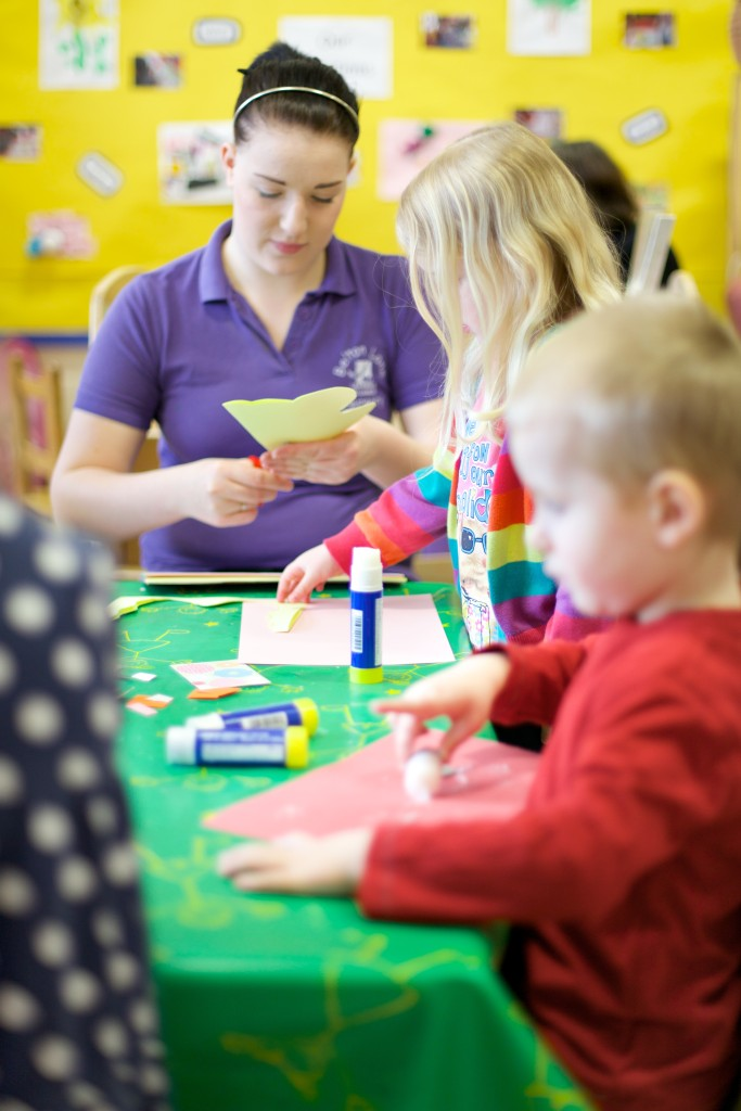 Pre-School Learning Alliance nursery worker doing crafts with children