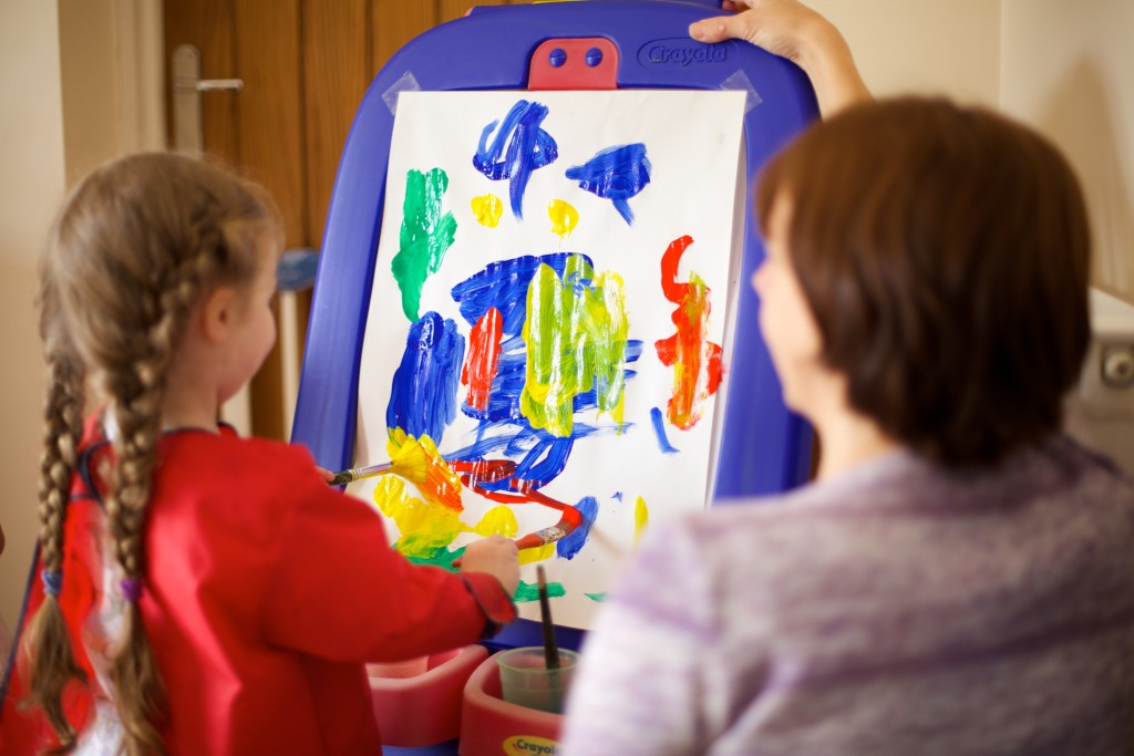 A toddler paints at a Pre-school Learning Alliance nursery