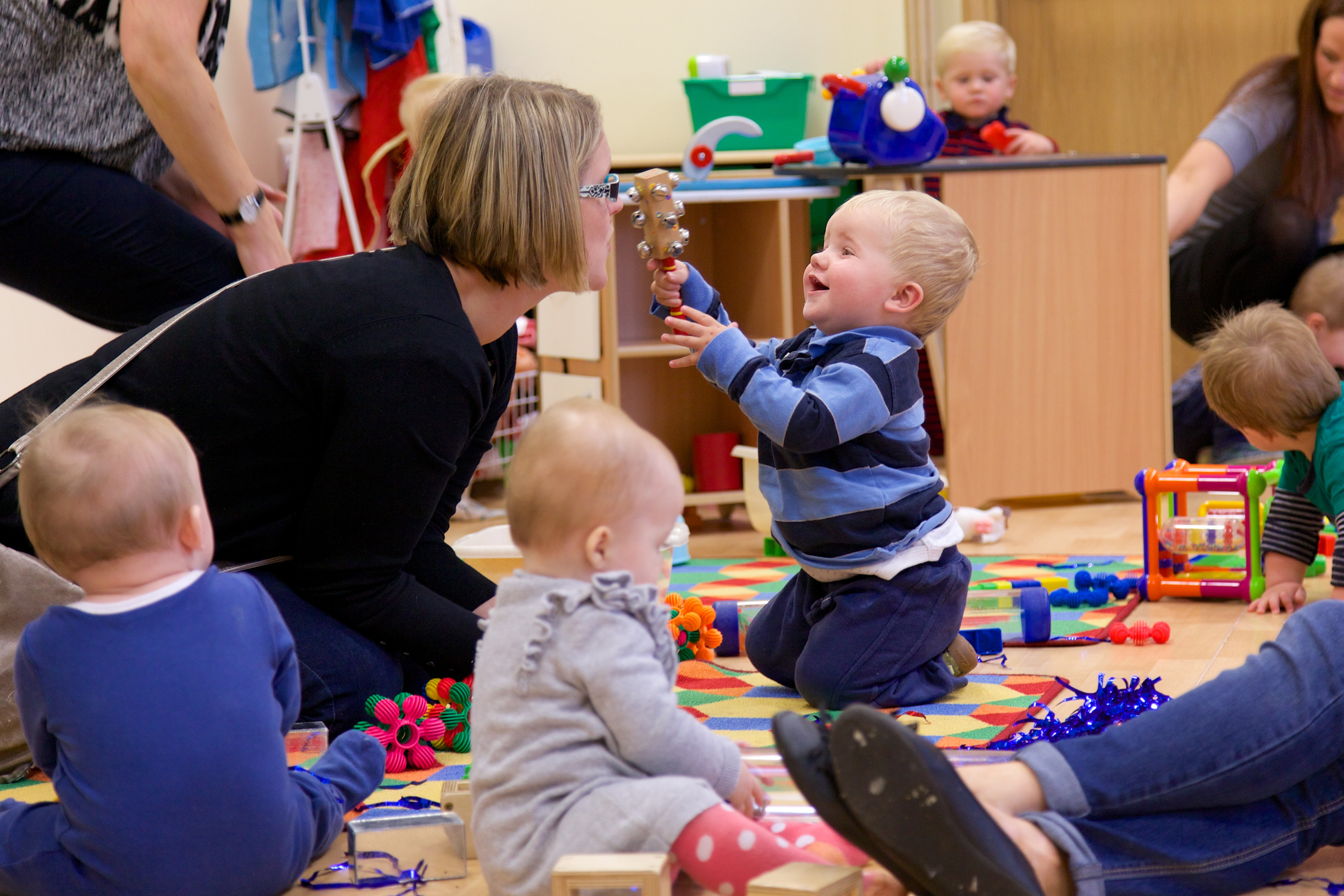 adult engaging with baby playing a music shaker
