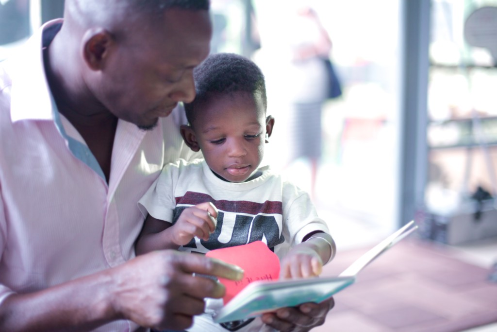 Man reads a book to his child
