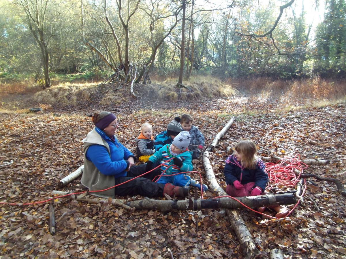 Julie and the children building in the forest with branches and rope