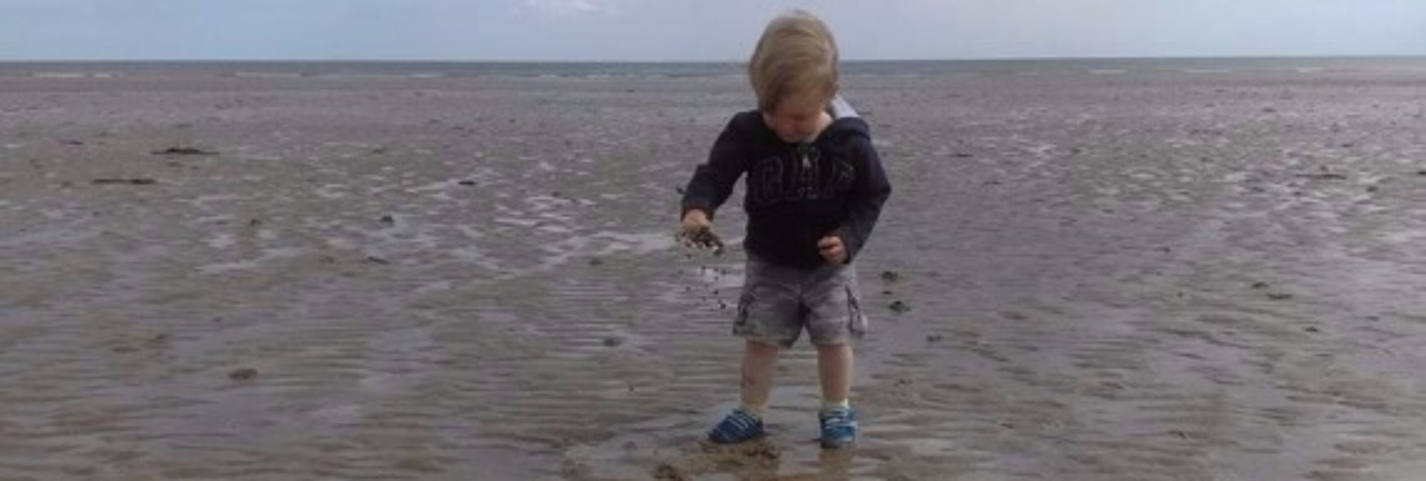 boy exploring wet sand