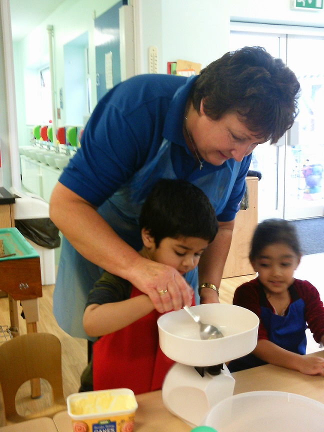 Nursery helper and child cooking together