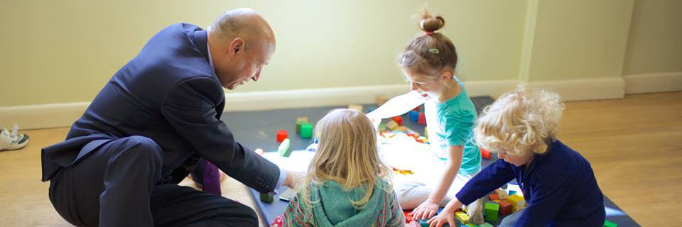 Neil Leitch plays with children at a nursery