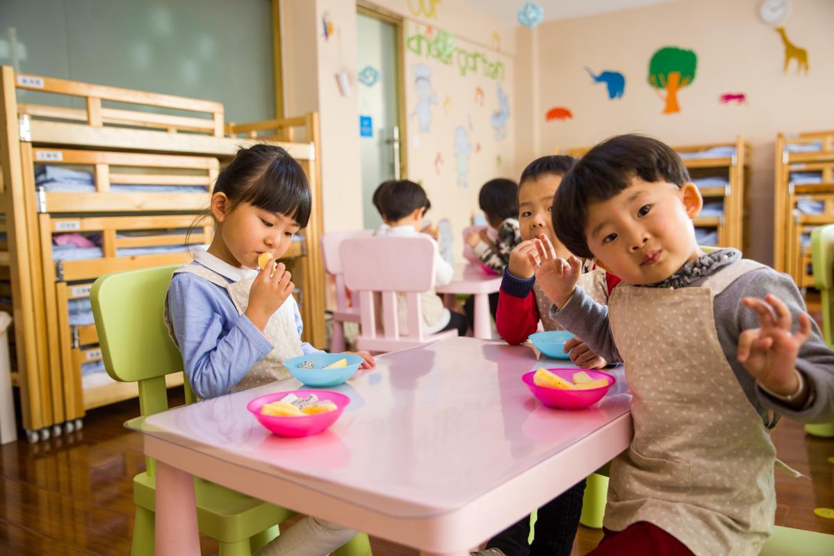 children enjoying fruit around a table