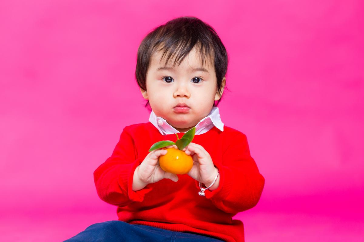a little boy holds a mandarin - considered good fortune in Chinese culture