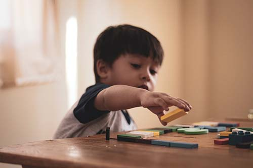 boy playing blocks childcare