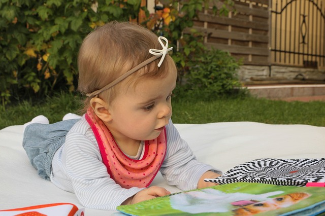 baby with book early reading skills