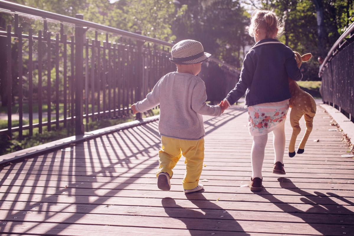 a boy and girl hold hands as they walk across a bridge