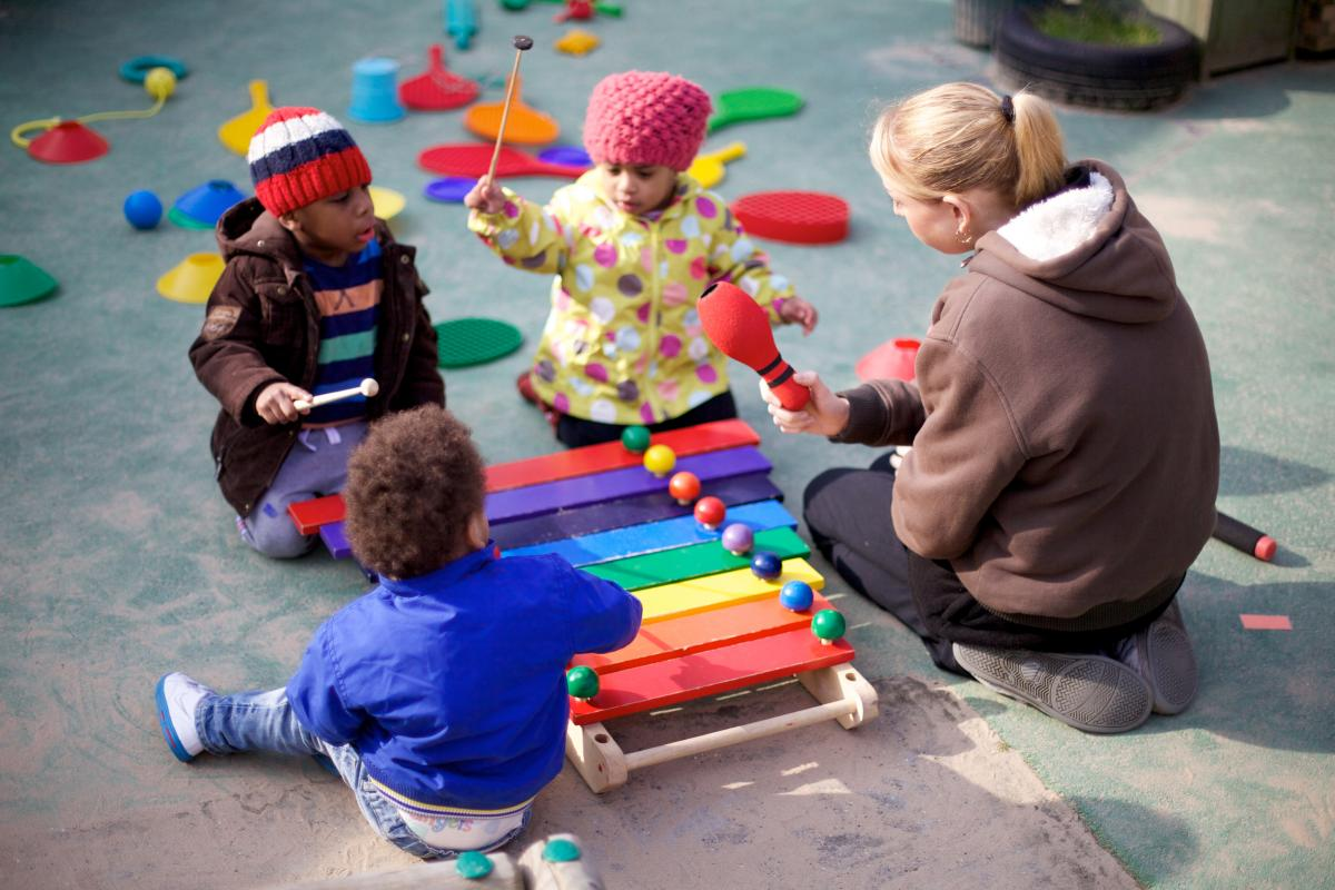 Three children play with a xylophone outdoors, whilst an adult watches