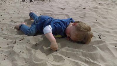 Boy, aged 2, explores dry sand