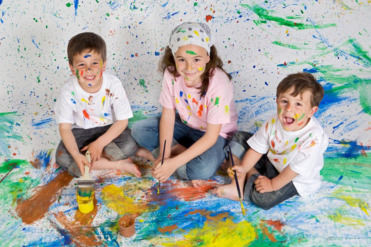 three children sit in messy play paint