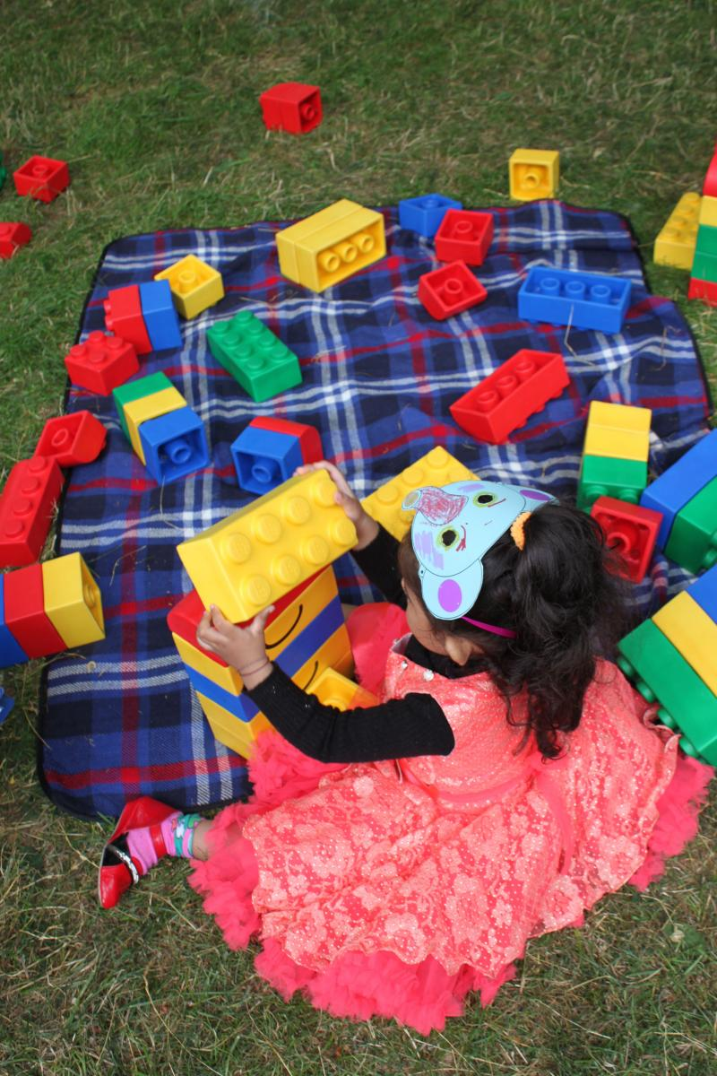 young girl plays with oversize lego