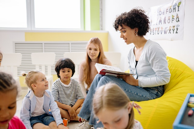 woman reading to nursery children early years business rates Wales