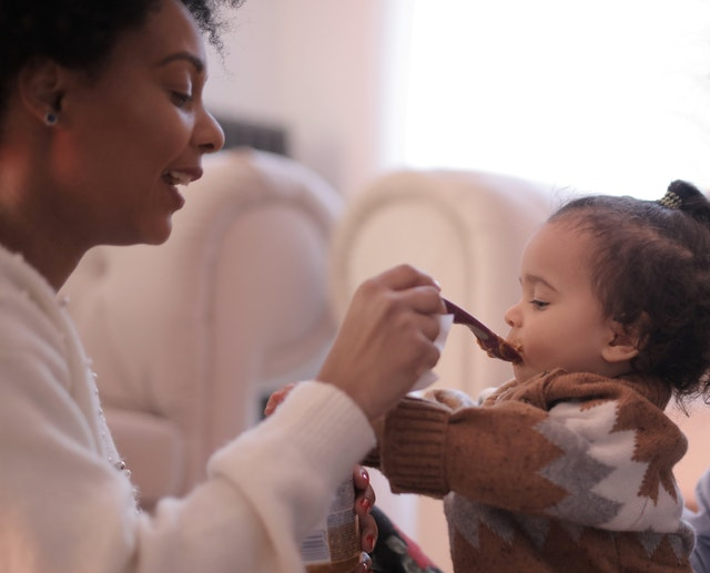 woman feeding toddler