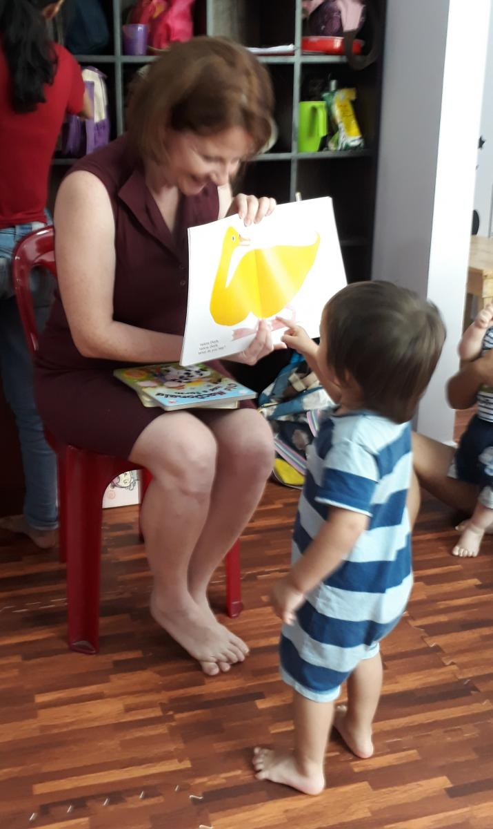 A parent and child enjoy looking at a book together