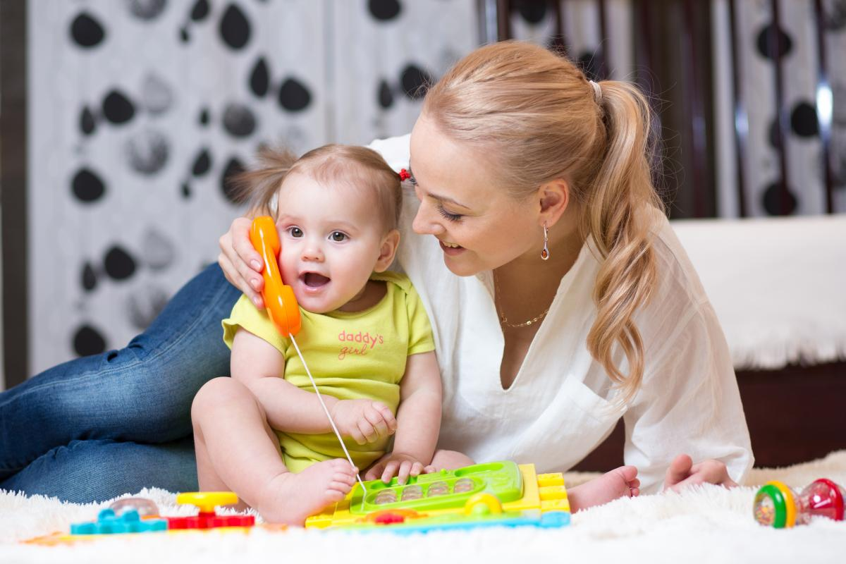 a mother plays with toddler and toy phone