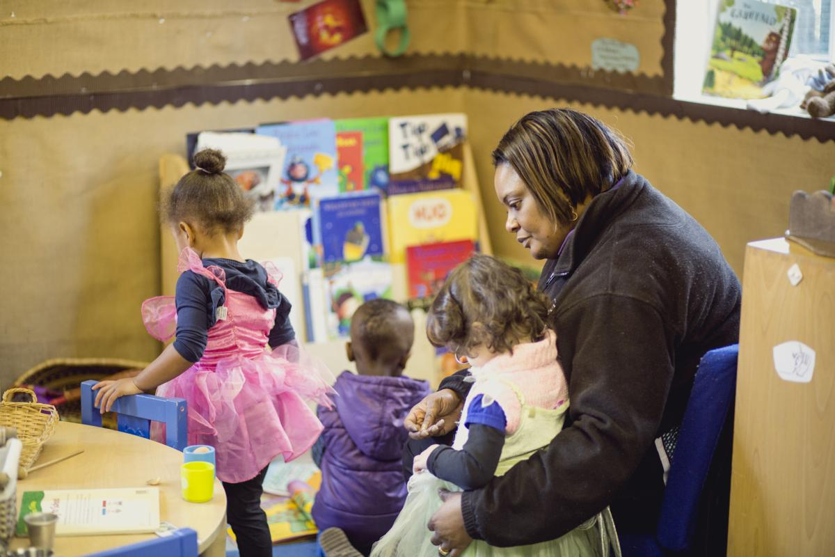 A nursery worker chats to some children