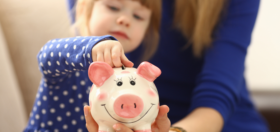 Girl putting coin in a piggy bank