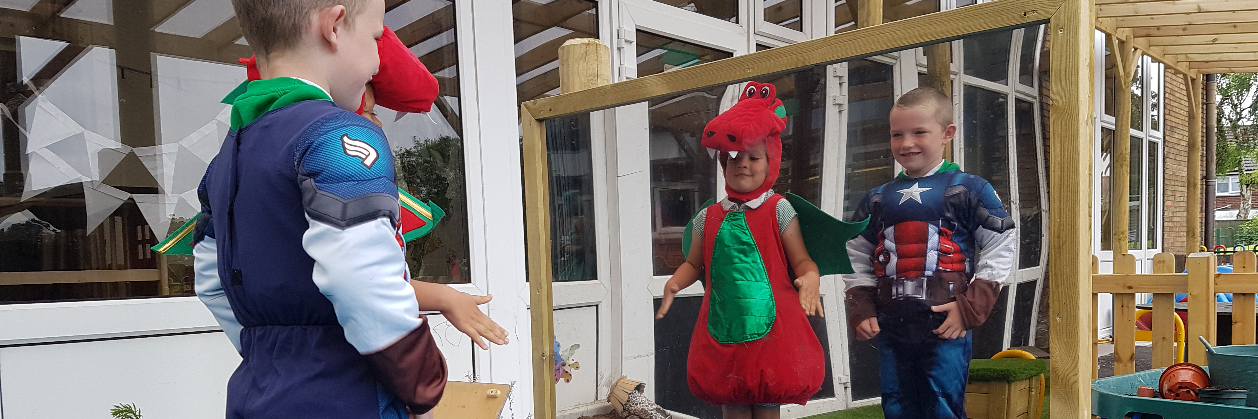 Two young children enjoy looking at themselves in large outdoor mirror