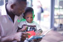 father reads to son sitting in his lap