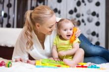 baby and mother play with toy phone