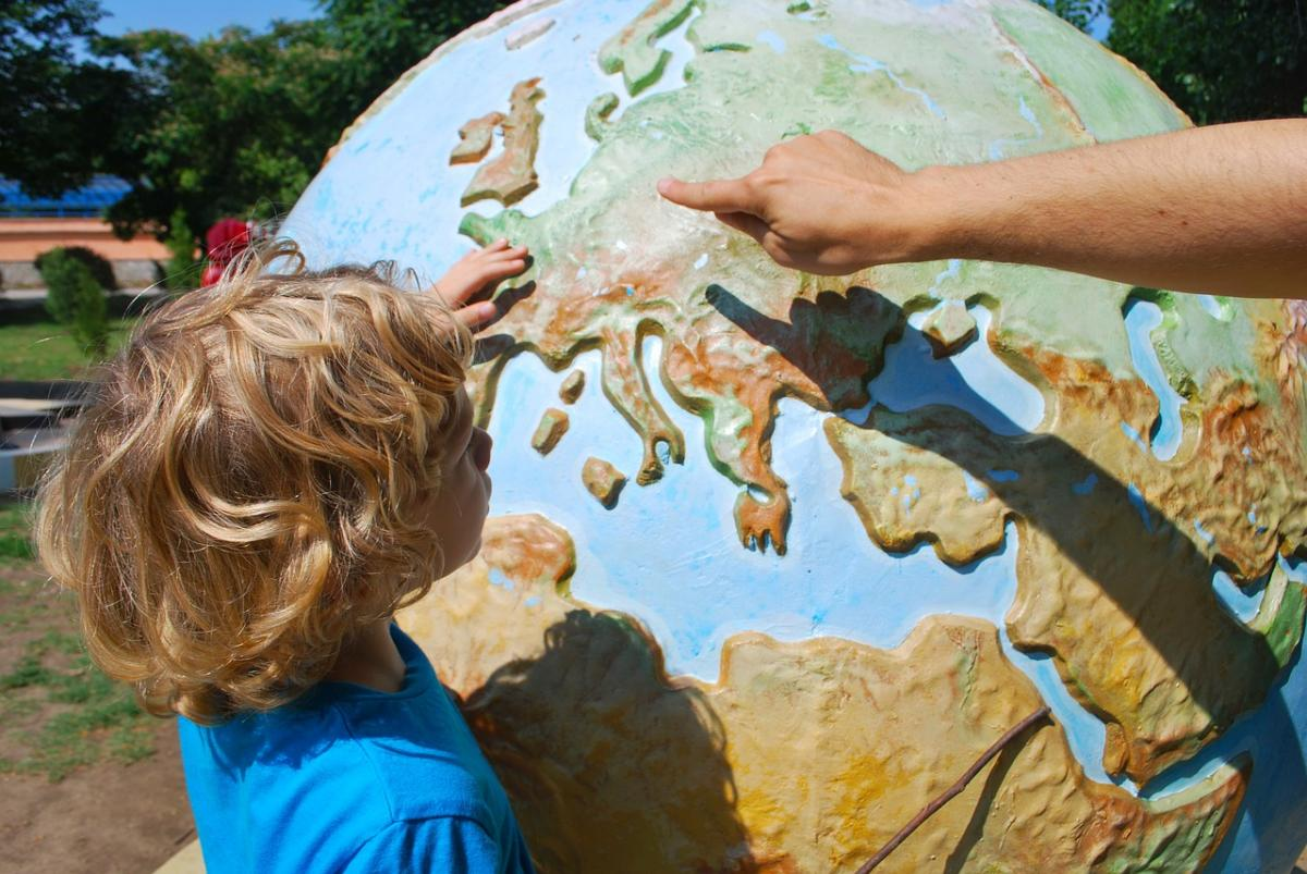Child being taught with a globe
