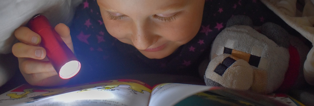 girl reading with torch