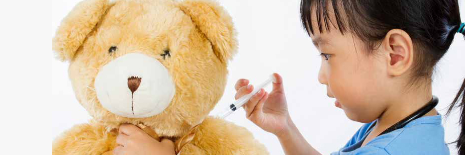 little girl gives injection to teddy bear