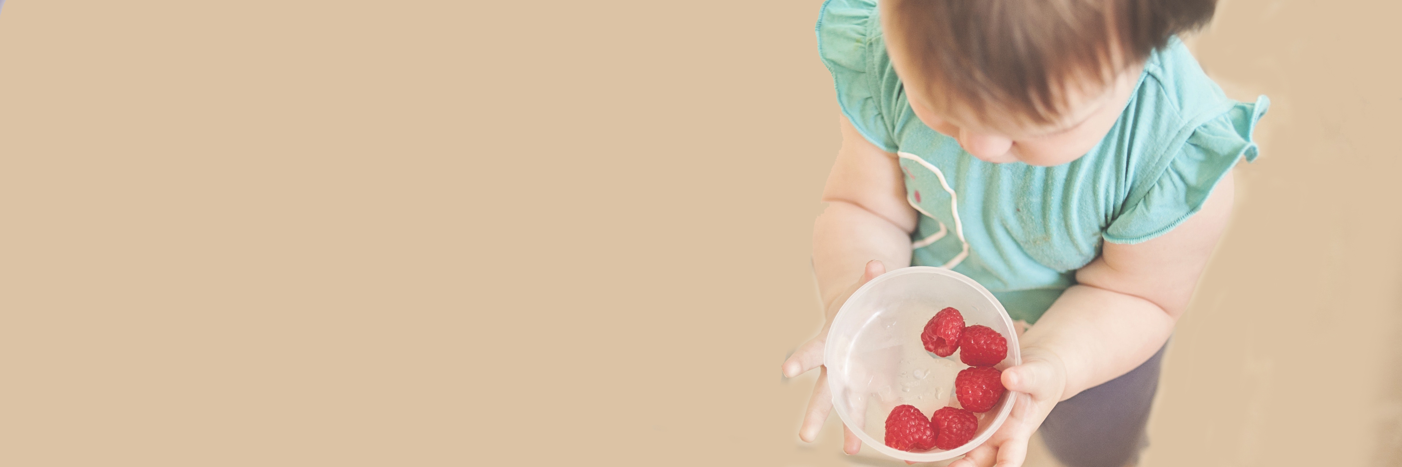 child with bowl of raspberries